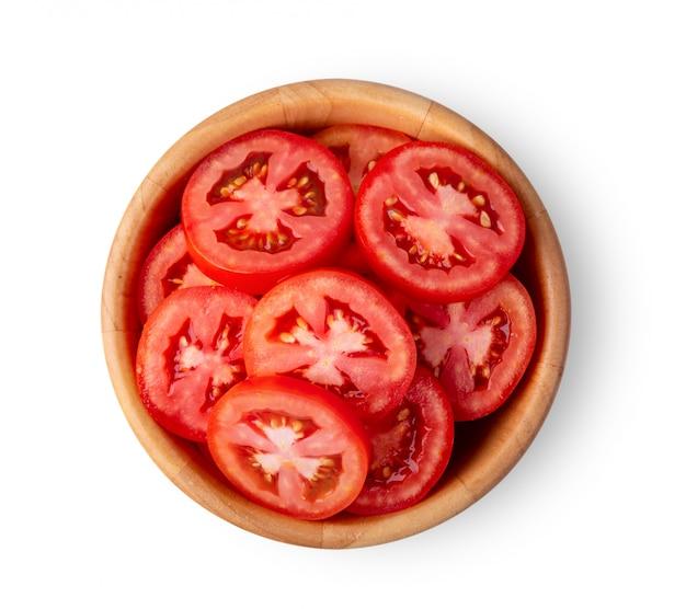 Rodaja de tomate en un tazón de madera aislado