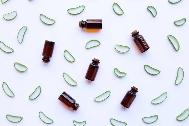 Rodajas de aloe vera con botella de aceites esenciales.