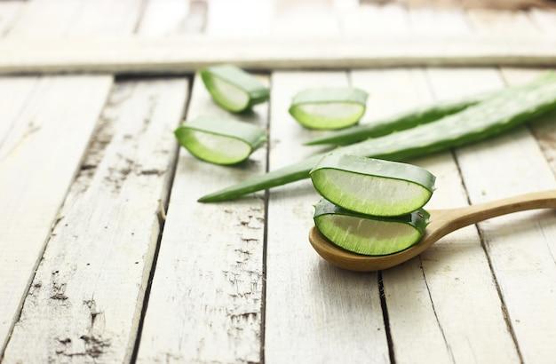 Rodajas de aloe vera en una cuchara de medicina a base de hierbas para la piel y el cabello en blanco