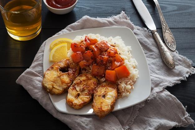 Rodajas de bacalao frito con arroz, limón y pimienta.