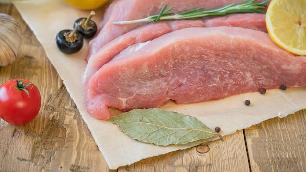Rodajas de carne de cerdo cruda con especias en una mesa rústica.