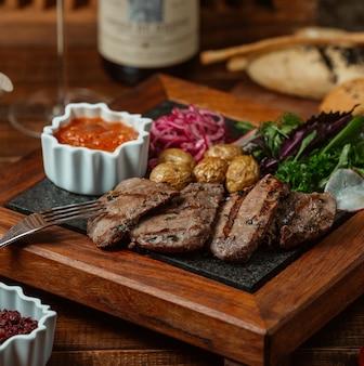 Rodajas de carne marinada a la parrilla servidas con papas baby, cebolla, ensalada de berenjena y hierbas