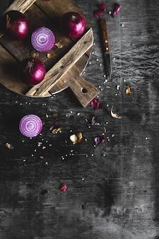 Rodajas de cebolla roja sobre tablero de madera con fondo oscuro