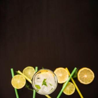 Rodajas de cítricos junto a vaso de bebida con hielo.