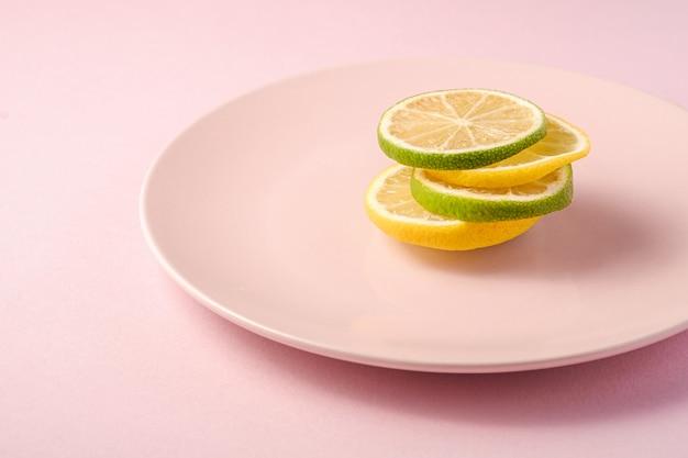 Rodajas de cítricos de limón y lima sabrosos frescos apilados en placa rosa, fondo mínimo aislado, ángulo de visión, macro