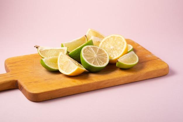 Rodajas de cítricos de limón y lima sabrosos frescos en tabla de cortar de madera, fondo rosa mínimo aislado, vista de ángulo