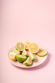 Rodajas de cítricos sabrosos frescos de limón y lima en placa rosa, fondo mínimo aislado, ángulo de visión
