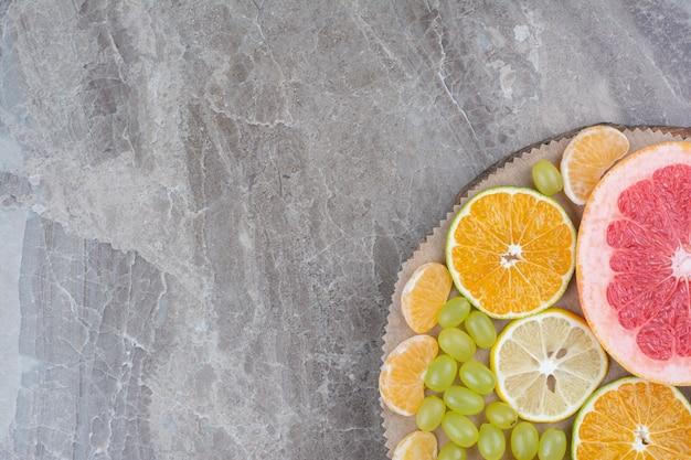 Rodajas de cítricos y uvas en pieza de madera.