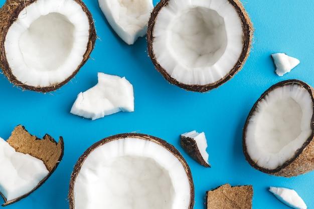 Rodajas de cocos tropicales rotos en azul