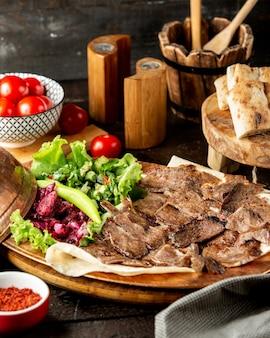 Rodajas de cordero doner servidas con ensalada de verduras y pan plano