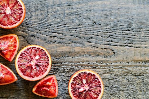 Rodajas y cortadas naranjas sanguinas sicilianas en madera natural, vista superior