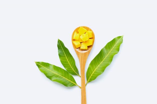 Rodajas de cubo de mango de fruta tropical con cuchara de madera y hojas sobre fondo blanco.