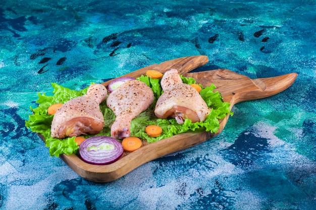 Rodajas de diversas verduras y muslos de pollo marinados en la tabla de cortar