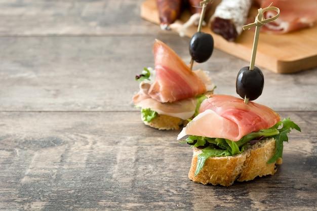 Rodajas finas brocheta de jamón serrano español con aceituna y lechuga en el espacio de copia de mesa de madera