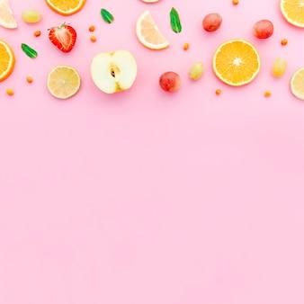 Rodajas de fresa manzana naranja uvas y hojas verdes