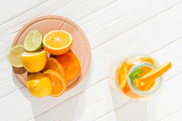 Rodajas de fruta con botella de limonada.