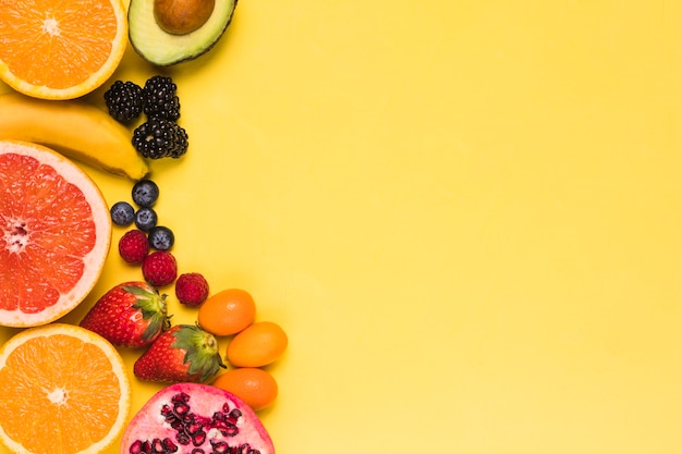 Rodajas de frutas y bayas sobre fondo amarillo
