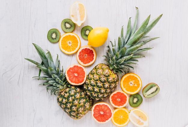 Rodajas de frutas cerca de piña cortada