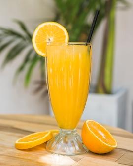 Rodajas de frutas cerca de vaso de bebida en la mesa