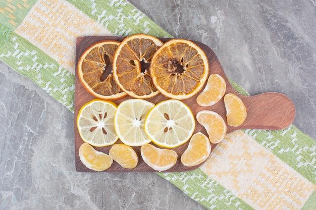 Rodajas de frutas cítricas en tablero de madera con mantel.