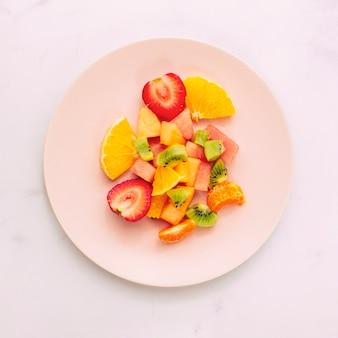 Rodajas de frutas exóticas maduras en plato.