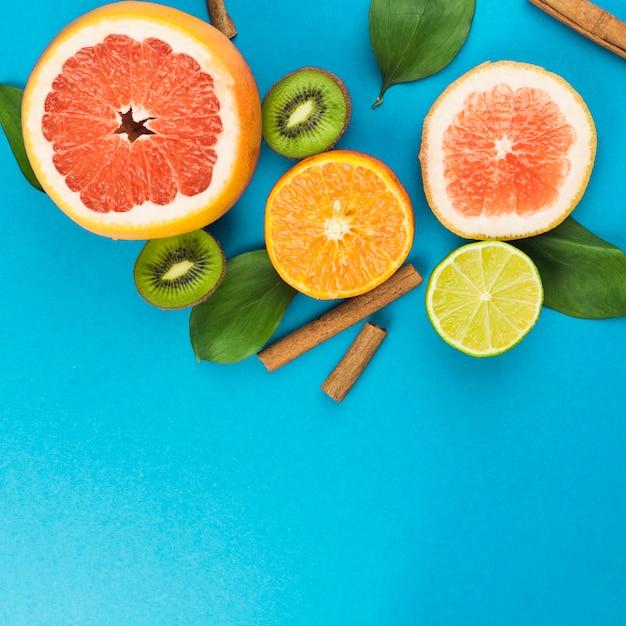 Rodajas de frutas frescas cerca de canela y follaje