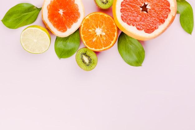 Rodajas de frutas frescas y follaje verde.