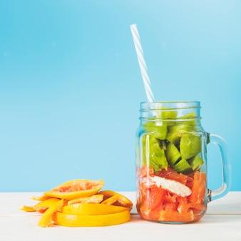 Rodajas de frutas frescas en frasco contra la pared azul