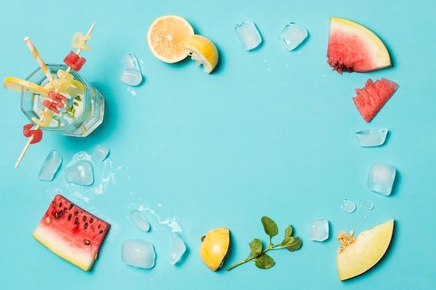 Rodajas de frutas entre hielo y título de verano sobre vidrio.