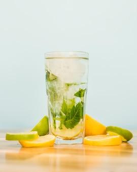 Rodajas de frutas junto a vaso de bebida con hielo y hierbas