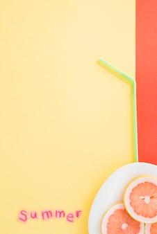 Rodajas de frutas en un plato cerca de paja y palabra de verano