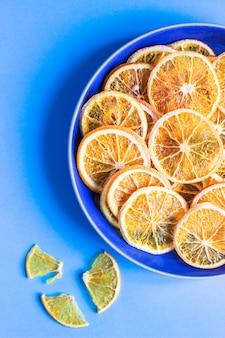 Rodajas de frutas secas de naranja sobre una placa de cerámica azul, papel azul concepto mínimo de fruta.
