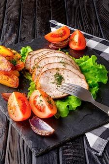 Rodajas de jamón al horno con tomates frescos en una placa de piedra en un estilo rústico