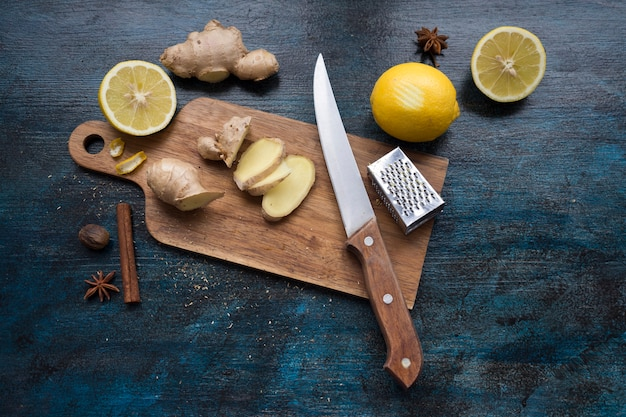 Rodajas de jengibre sobre tabla de madera con limón