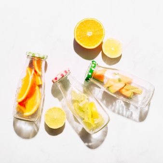 Rodajas de jugosas botellas de naranja y vidrio con cítricos cortados.