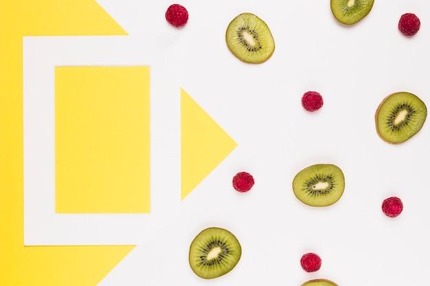 Rodajas de kiwi jugoso y frambuesa madura sobre fondo multicolor