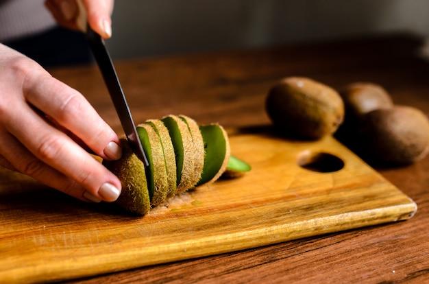 Rodajas de kiwi sobre una plancha de madera.