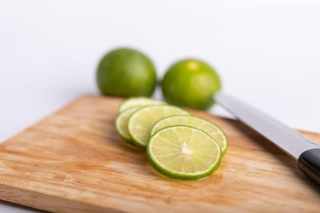 Rodajas de lima verde y semillas con un cuchillo en tabla de madera