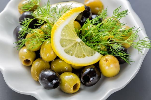 Rodajas de limón con aceitunas y eneldo de cerca
