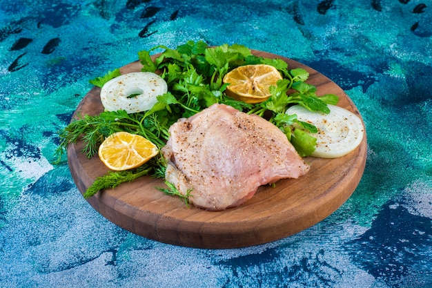 Rodajas de limón, cebolla y perejil con carne de pollo en una tabla