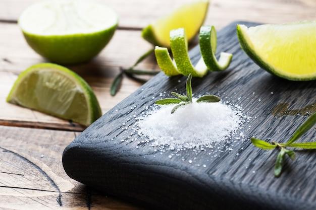 Rodajas de limón fresco, sal y romero en una tabla para cortar madera.