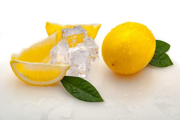 Rodajas de limón, hojas verdes, cubos de hielo frío y un limón amarillo entero fresco sobre un fondo blanco