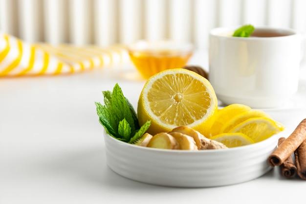 Rodajas de limón y jengibre con copyspace blanco menta. otoño, ingrediente de té de invierno