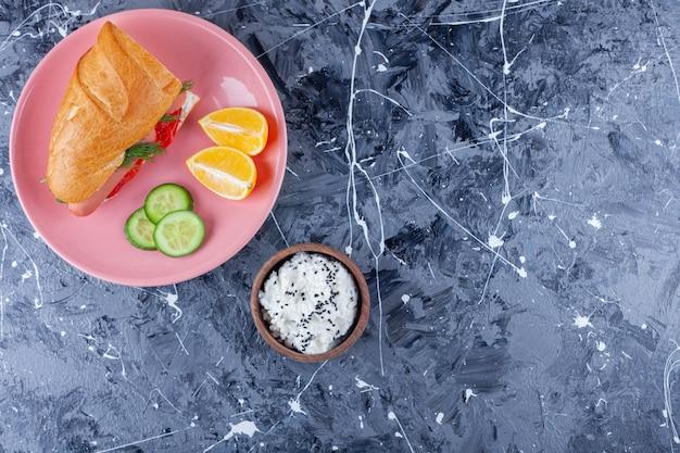 Rodajas de limón y pepino, sándwich en un plato junto a un cuenco de queso, sobre el fondo azul.