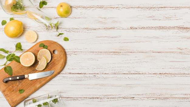 Rodajas de limones cerca de cuchillo entre plantas y vasos