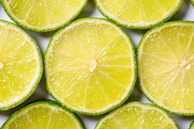 Rodajas de limones verdes jugosos frescos. fondo de textura, patrón.