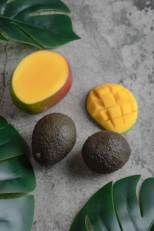 Rodajas de mango y aguacate maduros sobre superficie de mármol.