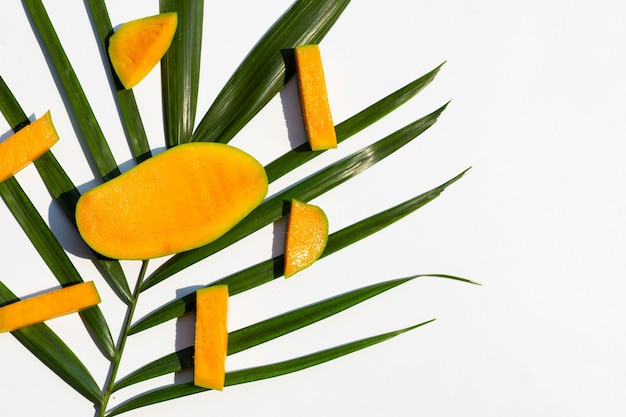 Rodajas de mango con hojas tropicales en blanco