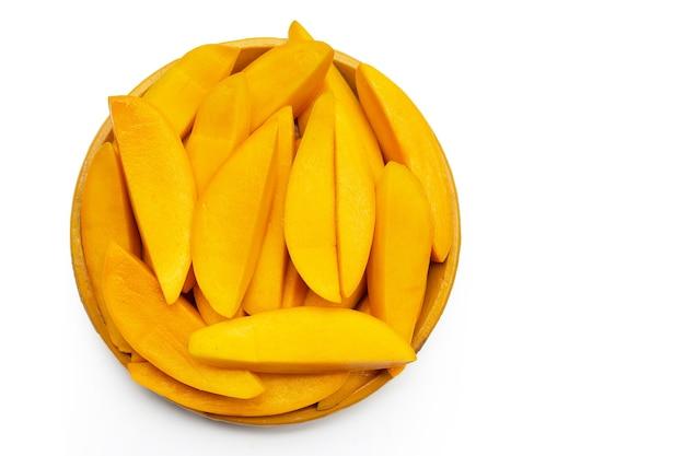 Rodajas de mango en placa amarilla sobre superficie blanca