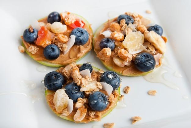 Rodajas de manzana con mantequilla de maní y arándanos. comida saludable.